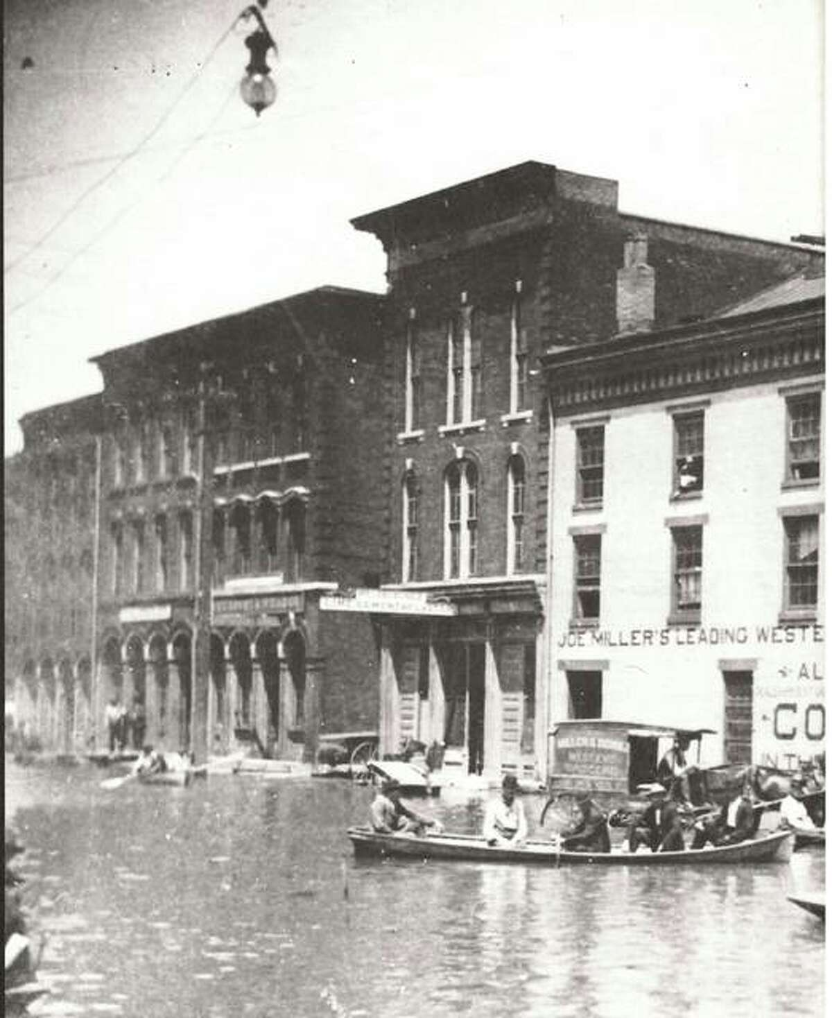 Joe Miller's West End Grocery was rather unique among groceries. The proprietors had to be prepared to fight flood waters from the Mississippi at least once a year. The store was the scene of feverish activity when floodwaters covered Second Street in 1903. The delivery wagon was in water up to its axles. The crowd was gathered to watch the floodwaters creep up State Street. This intersection was a popular place to mark the height of each year's flood. The H.K. Johnston Hardware Co. building carried the measurements of many floods until it was razed.
