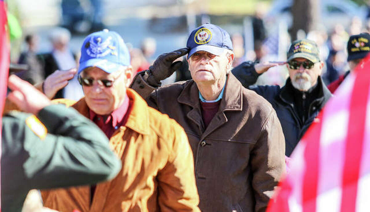 """Veterans salute after placing wreaths on graves Saturday at Alton National Cemetery during the annual Wreaths Across America ceremony. Assisted by students from St. Ambrose Catholic School students, 35 area veterans placed wreaths on 560 headstones for the ceremony, designed to """"remember, honor and teach."""""""