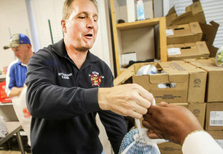 Alton Fire Department battalion chief Dave Eichen hands out turkeys Saturday at Crisis Food Center in Alton as part of a first-year community service program. The department donated $500 for the turkeys, matched by another $500 from the food pantry to feed 96 families. Photo: Nathan Woodside | For The Telegraph