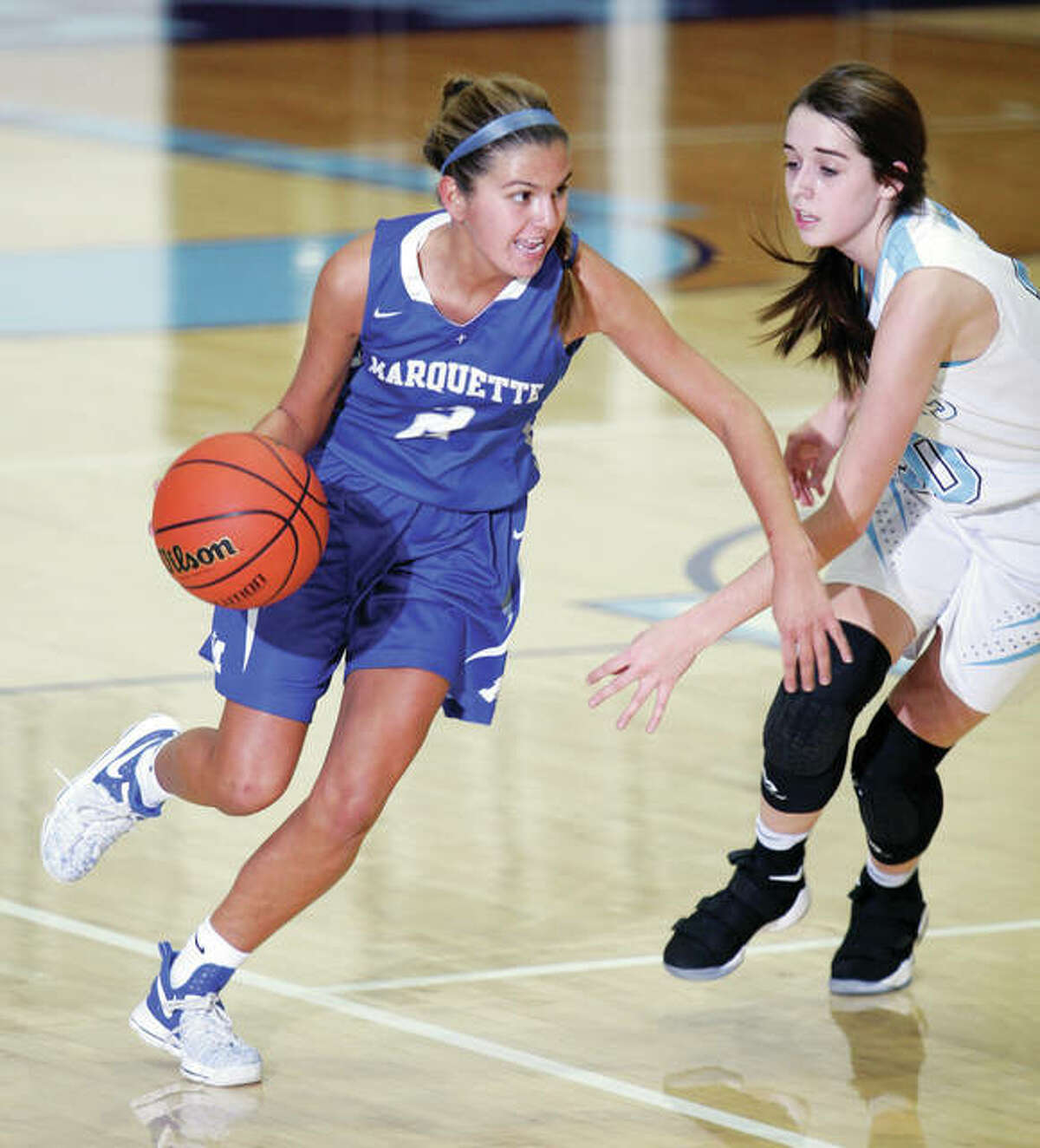 Marquette Catholic's Taylor Aguirre (left) pushes past Jersey's Abby Manns during an Explorers victory Dec. 6 game at Havens Gym in Jerseyville. The Explorers saw their winning streak ended at 10 in a row Saturday with a loss to Columbia at the Waterloo Gibault Tourney.