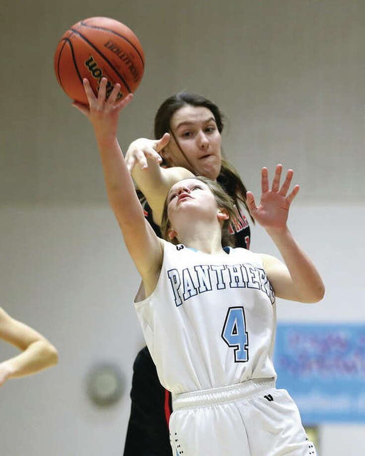 Jersey's Brianna Schroeder (front), shown scoring after getting past Triad's Caleigh Miller in a Mississippi Valley Conference game Thursday at Havens Gym in Jerseyville. On Saturday night, the Panthers were in Carrollton and Schroeder scored 11 points in a win over the Hawks. Photo: Billy Hurst / For The Telegraph