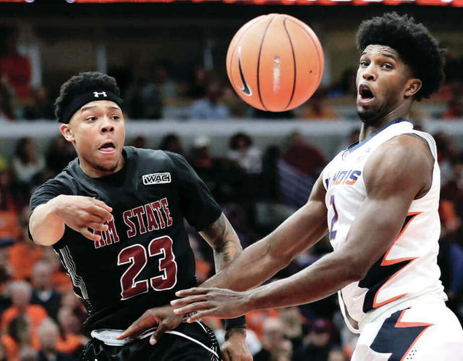 New Mexico State's Zach Lofton (left) passes around Illinois's Kipper Nichols during the first half Saturday night in Chicago. New Mexico State won 74-69. Photo: Associated Press