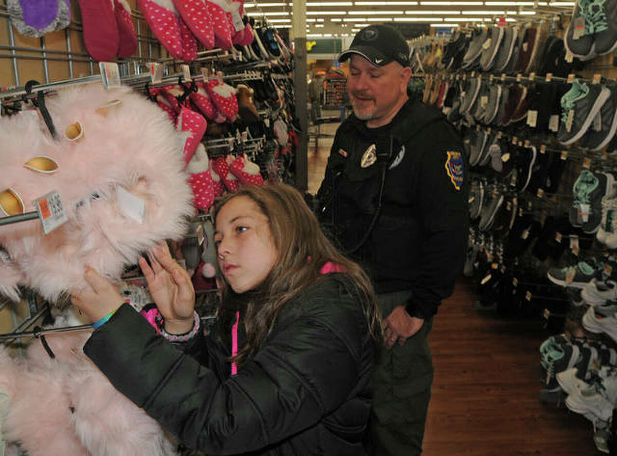 Officer Tim Bedard and Ayanette Jason examine some slippers during Shop With a Cop.