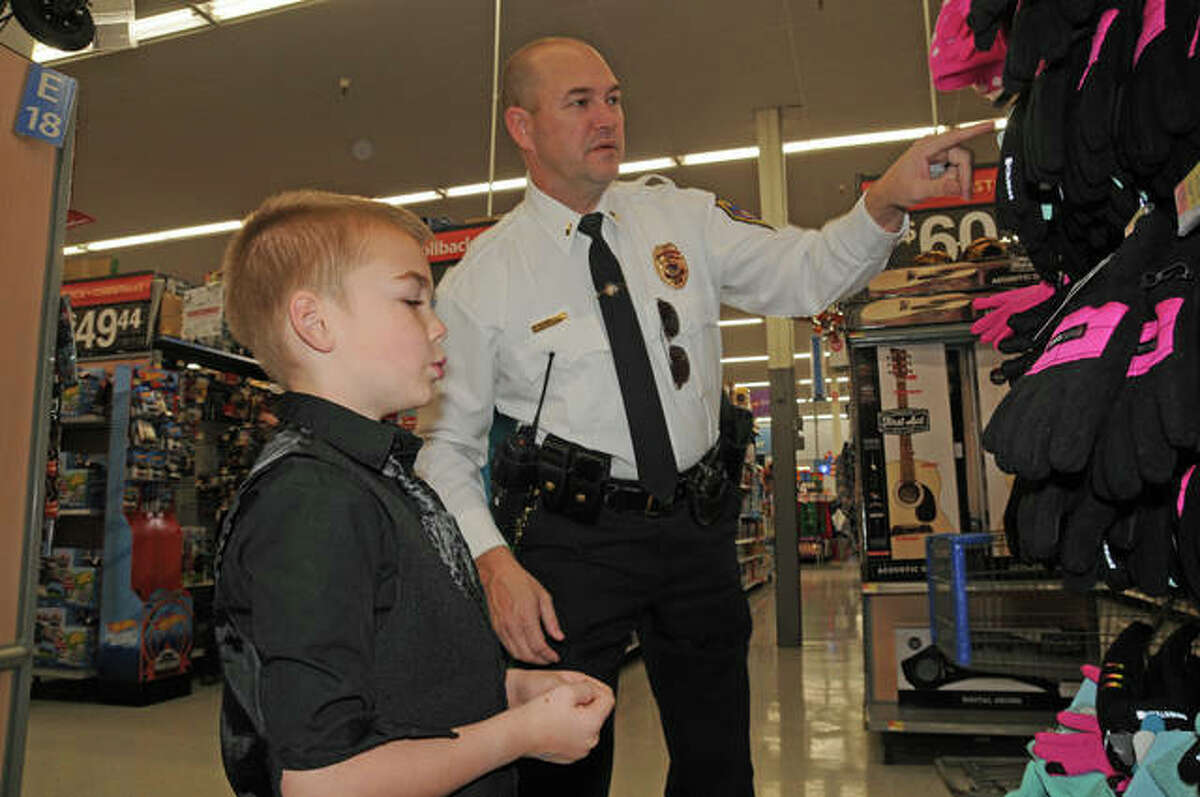 Officer Ken Wojtowicz helps Elijah Herrin shop for winter gloves.