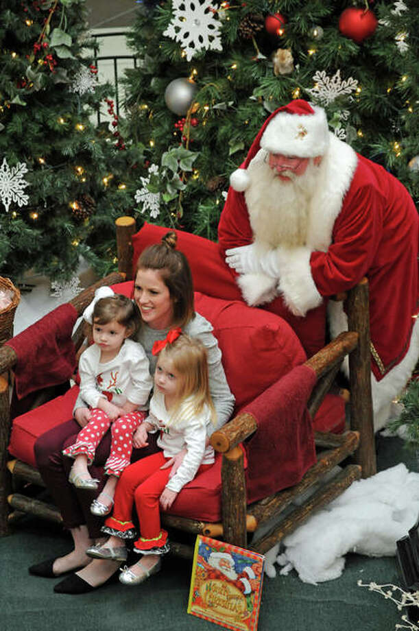 Sisters Farrah and Fallyn Lamb, of Carrollton, were shy of Santa Claus, so while they sat with their mother Rachel on Santa's chair, St. Nick sneaked in behind them so the family could get a good photograph.