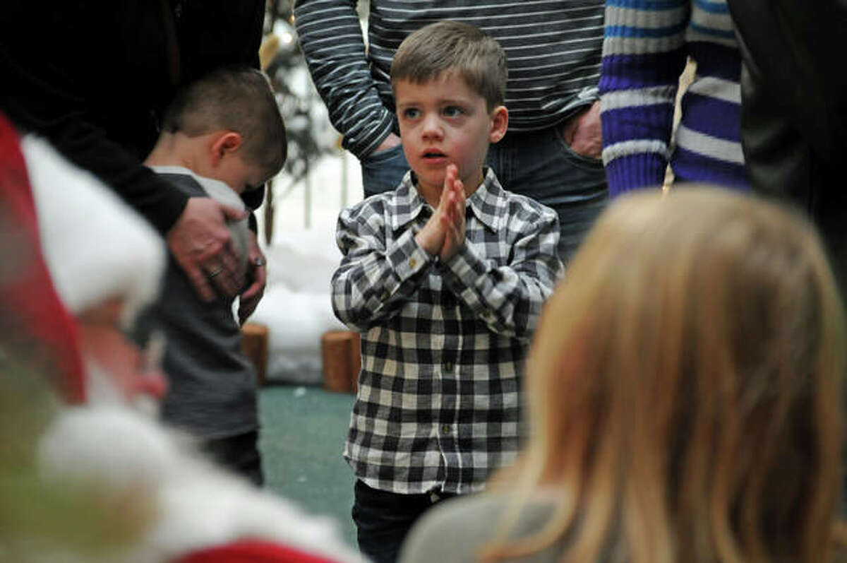 Four-year-old Mason Strader, of Edwardsville, can barely contain his enthusiasm as he is next in line to talk to Santa Claus on Sunday.