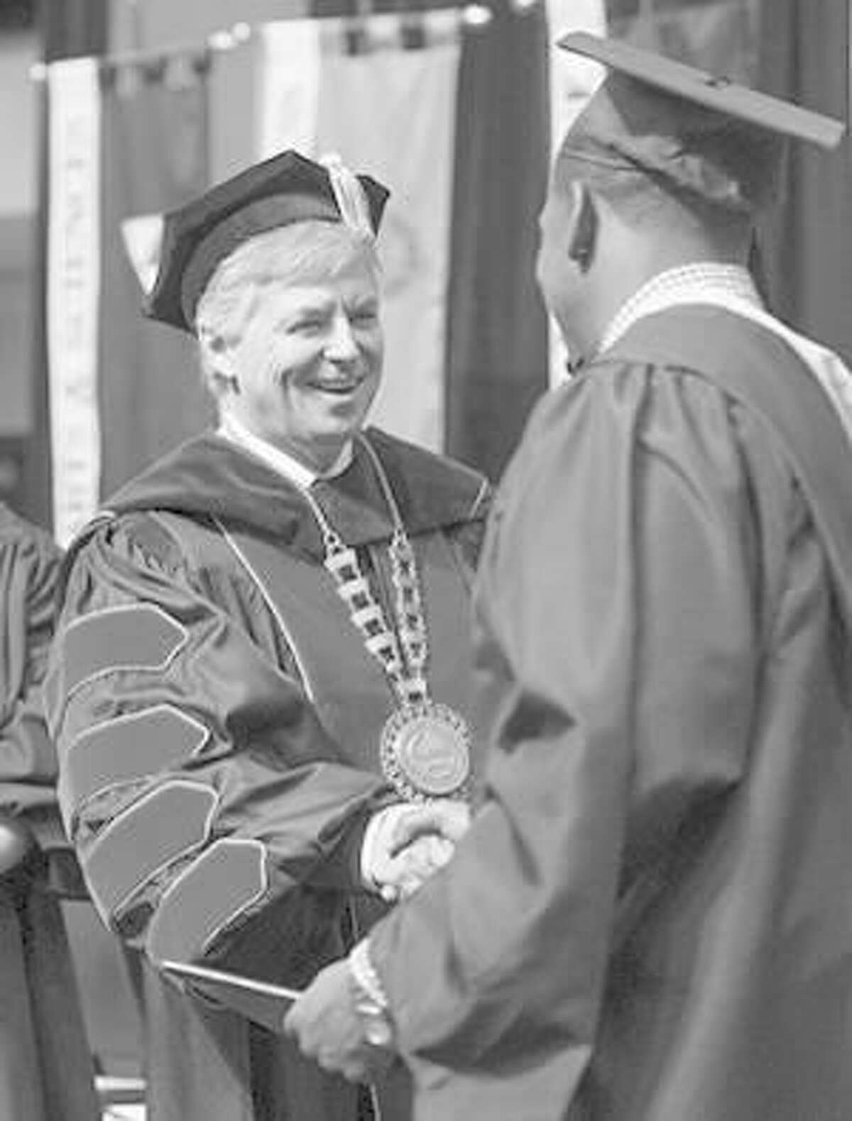 SIUE Chancellor Randy Pembrook congratulates a graduate at the school's fall commencement Saturday.