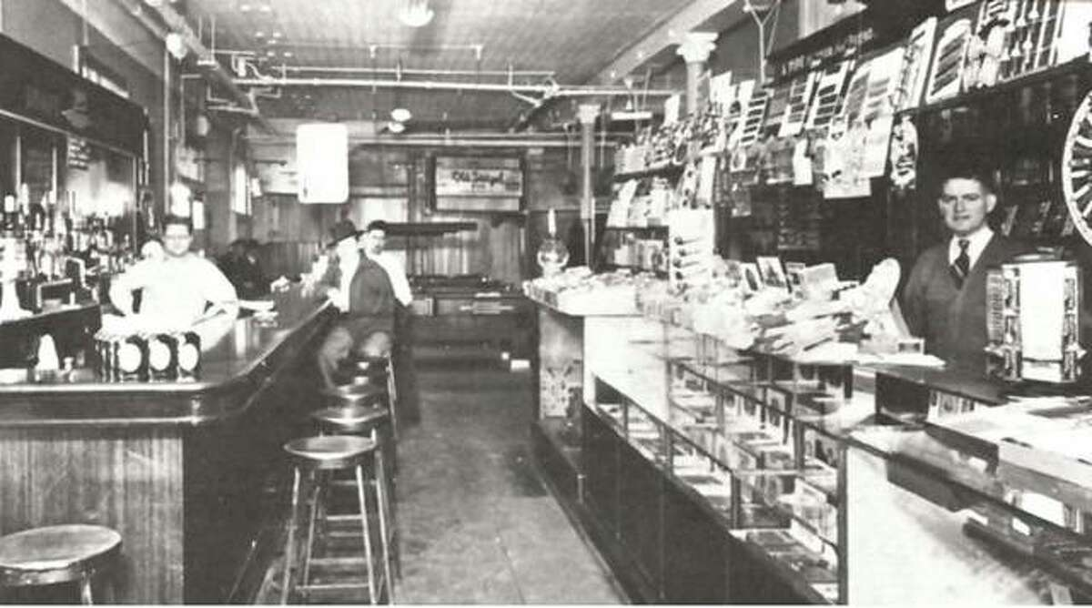 """Joseph C. Faulstich leased the first floor of the Laura Building in 1916, for the purpose of opening a cigar store and factory, news agency and billiard room. His rent was to be $120 per month. Faulstich purchased the building in 1920, and renamed it the Faulstich Building in 1923. The interior of the store contained a bar and cigar counter. The large """"back room"""" contained several pocket billiard tables and provided many hours of entertainment for the men and boys of Alton. As in other places of this kind, there were the players, and the spectators."""