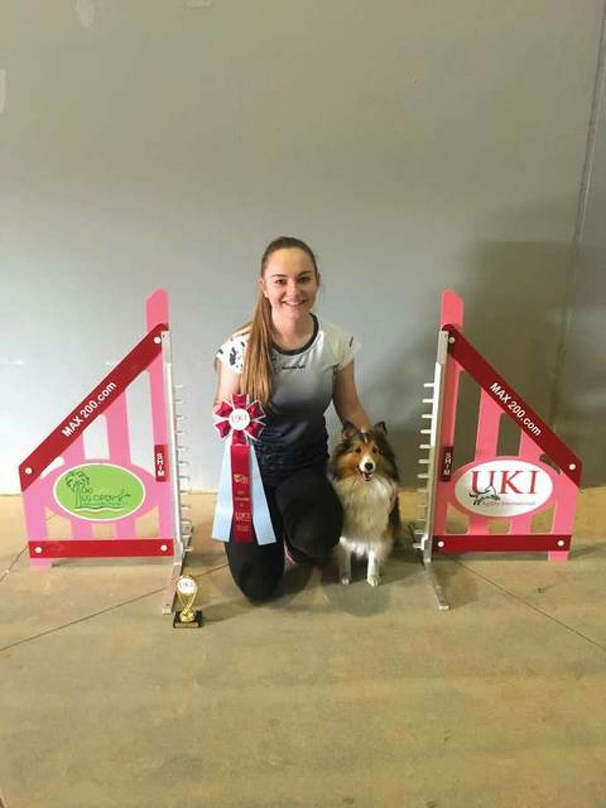 Lydia Carnes and her Shetland sheepdog, Bella, with one of the awards they have won.
