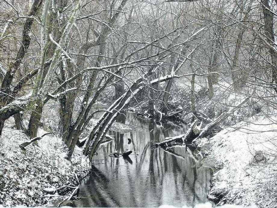 A snow-shrouded creek looks calm but serves as a reminder that winter is not yet over. Snow that moved into west-central Illinois early this week has largely melted, but it is being followed by bitterly cold temperatures.