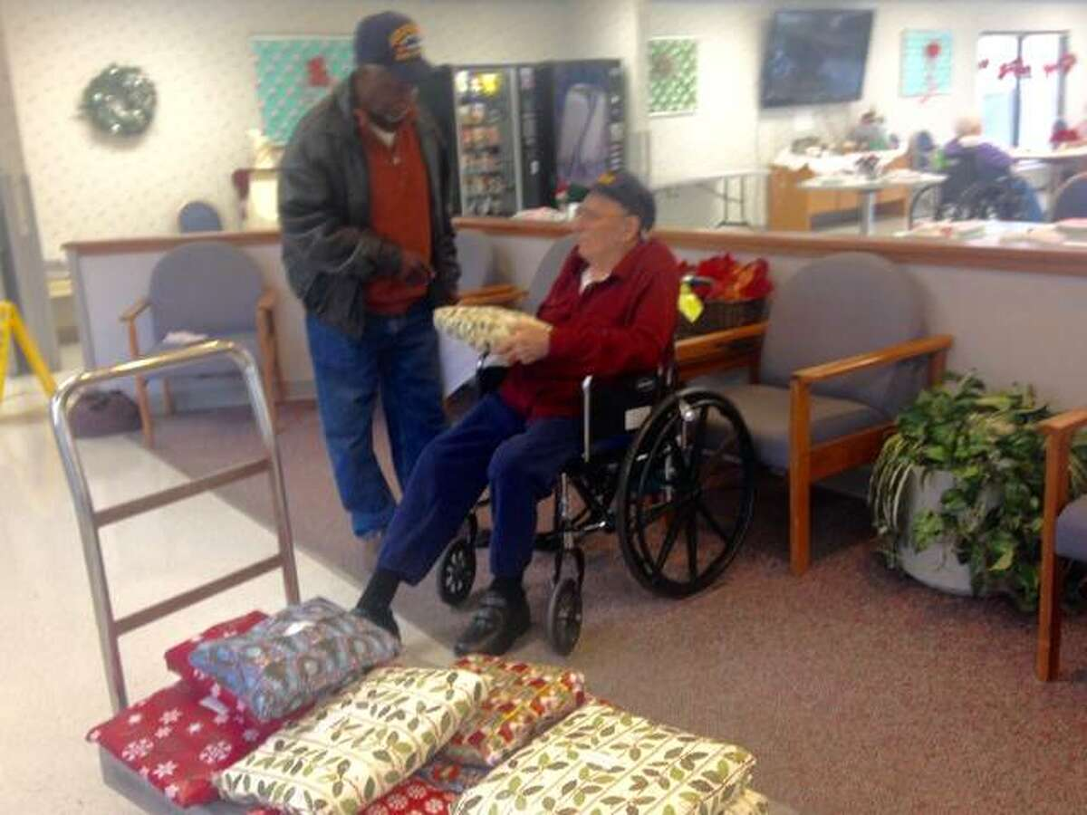 Joe Brice, commander of Allen Bevenue American Legion Post 354 of Alton gives a Christmas present to veteran Larry Mueller, 91, at Rosewood Care Center. Brice brought gifts to 18 veterans at the long-term care facility. Linda N. Weller/The Telegraph