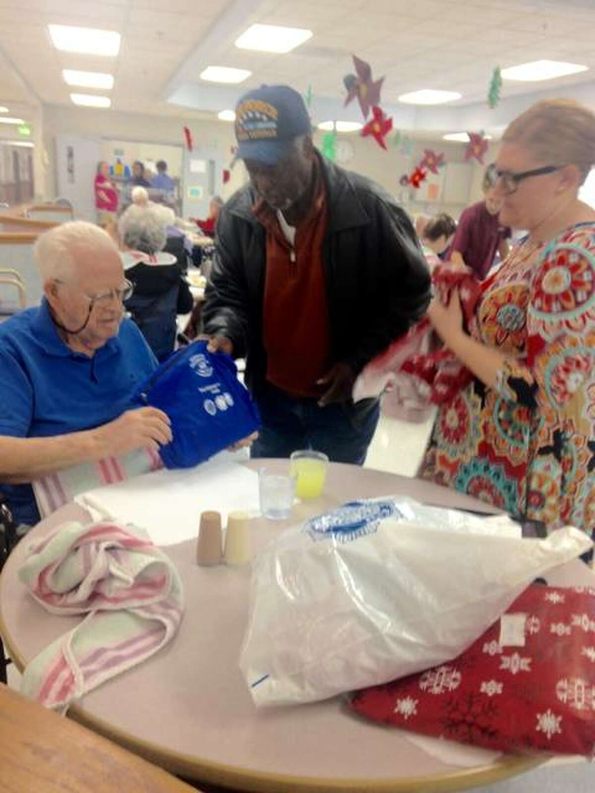 Clifford Barnes, 91, opens a gift containing several items in a bag from Joe Brice, commander of Allen Bevenue American Legion Post 354 of Alton, at Rosewood Care Center. Brice brought Christmas gifts to 18 veterans at the long-term care facility, and 100 presents overall to residents of five area nursing homes. Activities Director Frances Allen, right, assisted some of the men in opening their presents. Linda N. Weller/The Telegraph