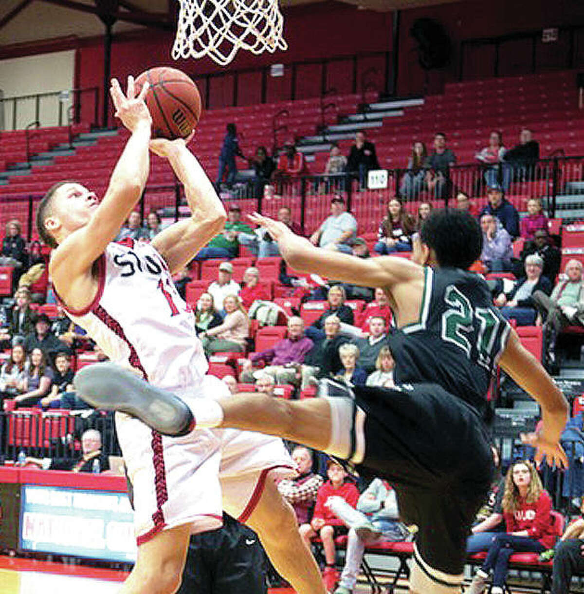 SIUE's Christian Ellis, left, puts up a shot over Chicago State's Cameron Bowles (20) in action Tuesday night at the Vadalabene Center. Ellis scored 19 points and SIUE won 88-76
