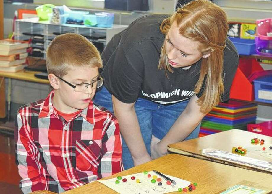 Waverly Elementary School second-grader Case Brown gets his math bingo board looked over by junior Sylvia Davis during the Pi Day on Tuesday. Photo: Samantha McDaniel-Ogletree | Journal-Courier