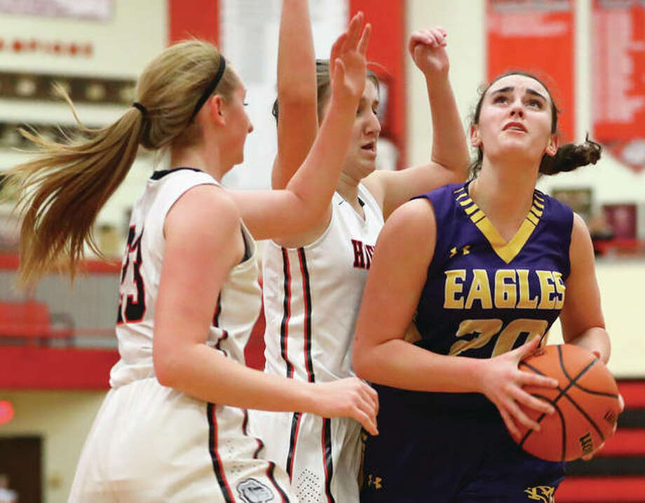 CM's Anna Hall (right) drives through heavy traffic in the lane before shooting over Highland's Mae Riffel and Lauren Baer (left) during Wednesday night's Mississippi Valley Conference girls basketball game in Highland. Hall, a sophomore, scored a career-high 21 points in the Eagles' 52-25 win. Photo: Billy Hurst / For The Telegraph