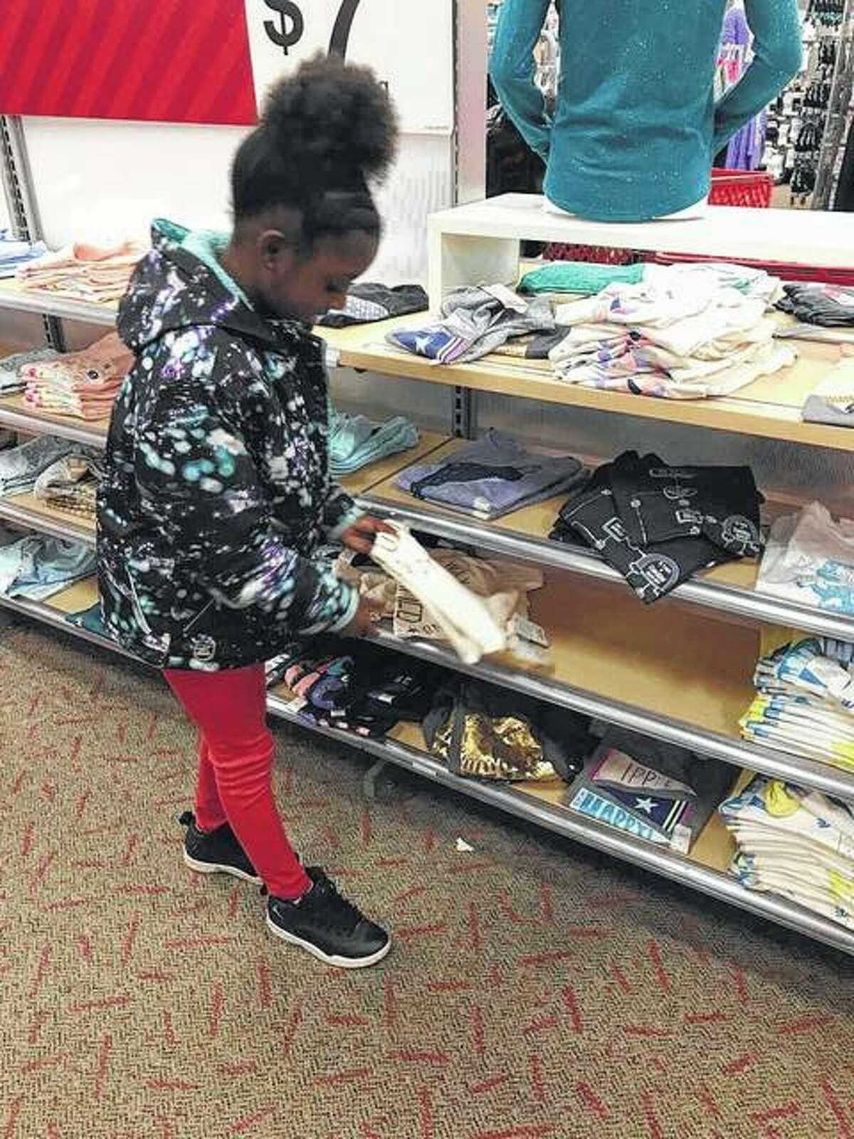 """Kya Ingram, 9, shopped with her family looking for """"clothes first, then toys,"""" at the annual NAACP shopping spree hosted at the Alton Target. A total of 48 children were given $100 to shop for toys or clothes for either themselves or for their family members."""