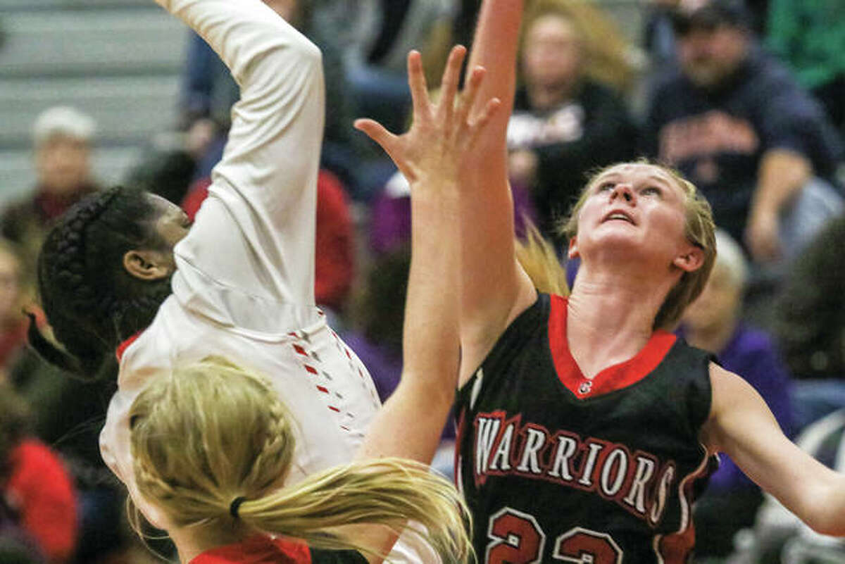 Calhoun's Junie Zirkelbach (right) battles an Alton player for a rebound during a Nov. 15 game at the Alton Tip-Off Classic on Nov. 15 in Godfrey. Zirkelbach was back home in Hardin on Wednesday night and scored 28 points in the Warriors' overtime victory over the Liberty Eagles.