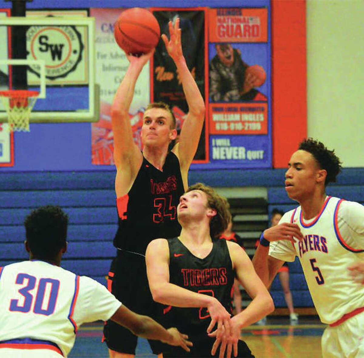 Edwardsville's Caleb Strohmeier (back) shoots behind a screen set by teammate Jack Marinko while East St. Louis' Joe Reece (right) and Imunique Williams (30) defend during Wednesday night's Southwestern Conference boys basketball game in East St. Louis.