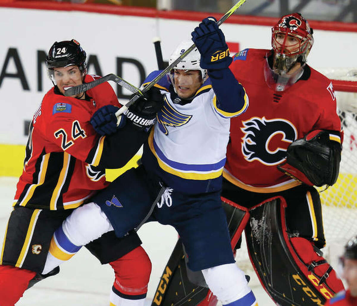 The Flames' Travis Hamonic (left) tries to move the Blues' Scottie Upshall from blocking Flames goalie Mike Smith during the first period Wednesday night in Calgary, Alberta.
