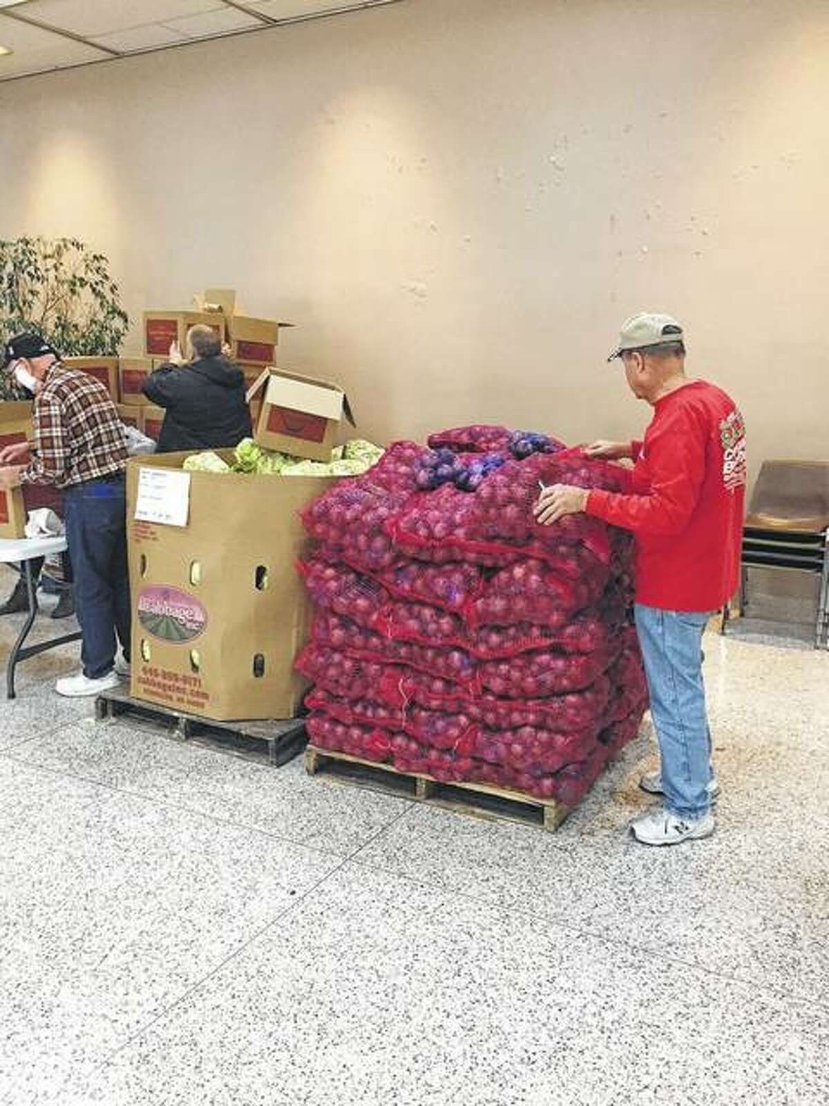 Volunteers help sort loads of potatoes, cabbage and other food items.