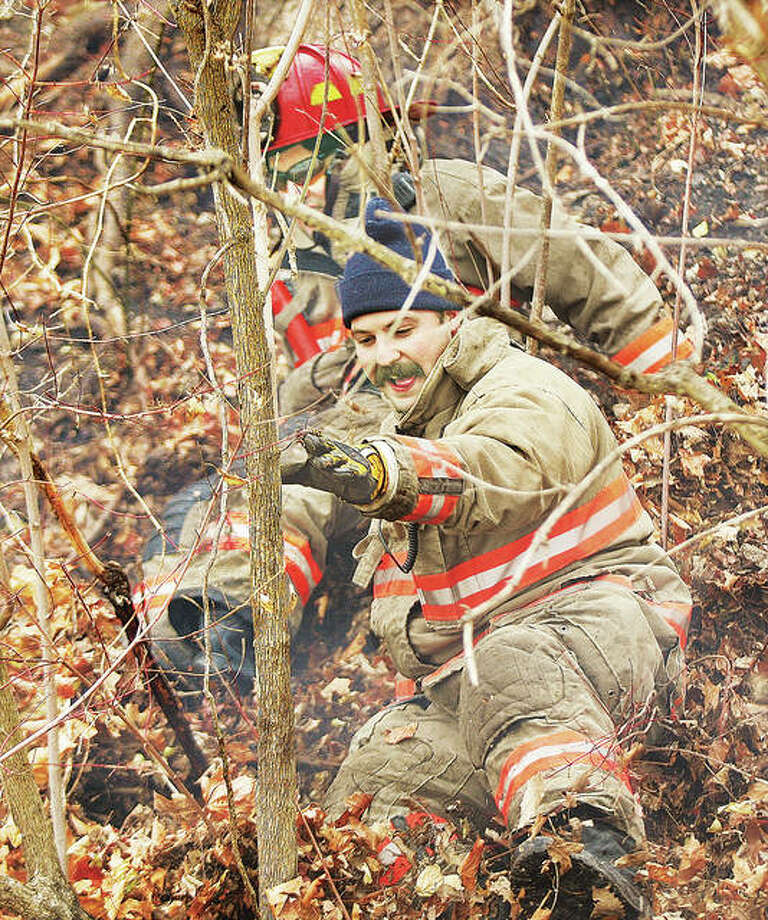 What goes up must come down, according to the law of gravity. Firefighters were learning that first hand again Thursday, as sliding down the side of the bluff was about the only way to get down after climbing up about 60 feet to attack the flames with a hose line. Photo: John Badman | The Telegraph