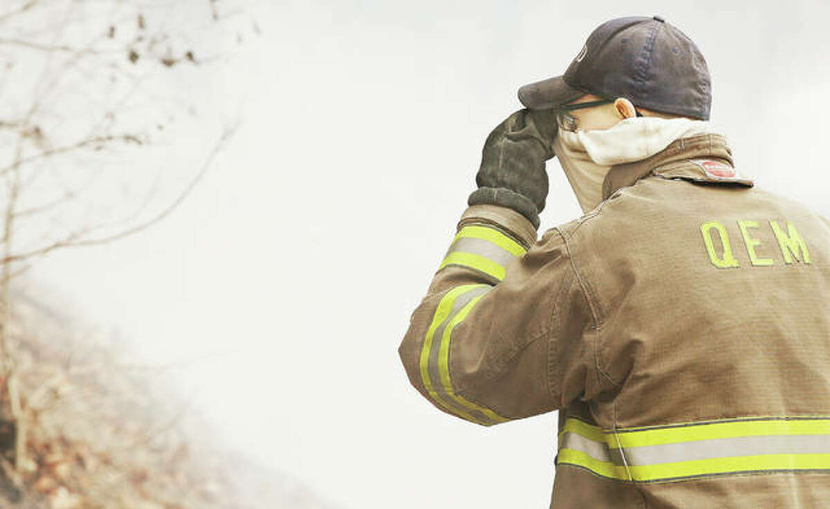 A QEM Fire Protection District firefighter pulls his neck covering up over his nose Thursday to lessen the smoke he was breathing in from a fire burning the bluffside on the Great River Road about two miles west of Lockhaven Road in Jersey County. The fire, swept by winds from the river, has been burning for days.