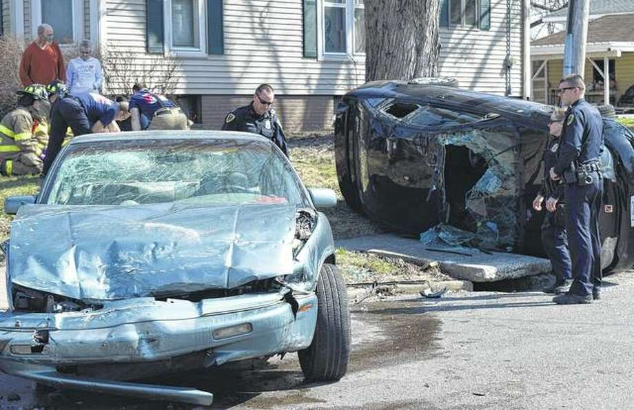 Two people were injured Friday afternoon in a crash at South West and West Chambers streets. A man and a woman were taken to Passavant Area Hospital after the collision, which caused one car to flip on its side and get pinned against a utility pole. Names and details about those injured were unavailable Friday evening as police investigated. Photo: Greg Olson | Journal-Courier