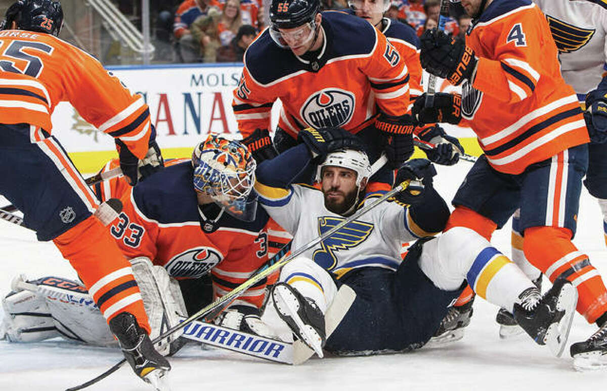 The Blues' Chris Thorburn (middle) crashes into Oilers goalie Cam Talbot during the first period Thursday night in Edmonton, Alberta. The Oilers beat St. Louis 3-2.
