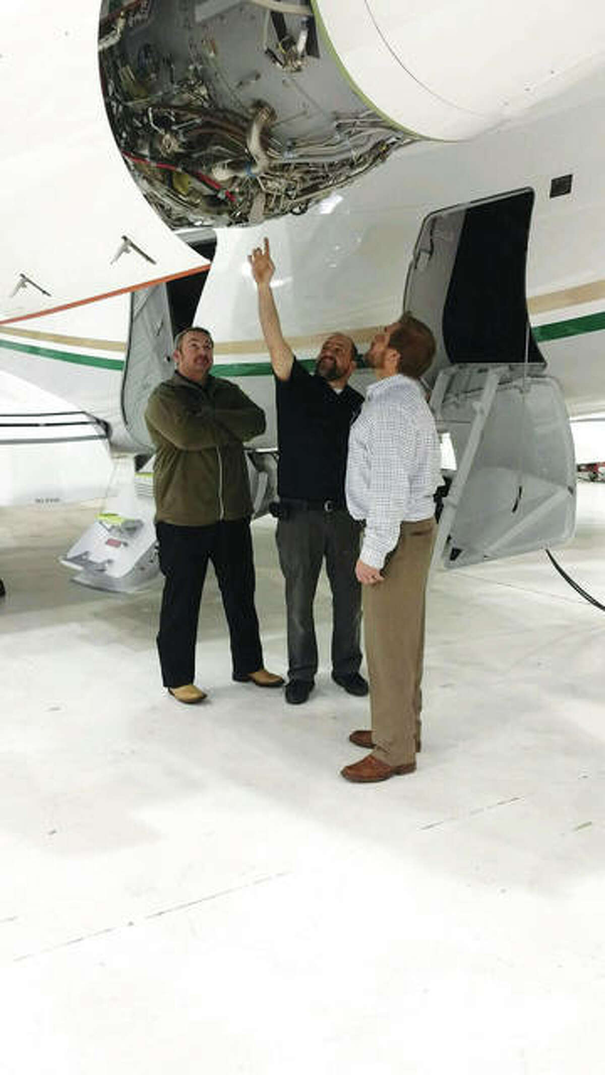 Falcon Technical Sales Manager Ryan Gibbs, left, Falcon Program Manager Garret Heisler, center, both of Worden, and West Star Aviation General Manager Eric Kujawa, of East Alton, look over a corporate jet located in West Star Aviation's existing maintenance, repair and overhaul hangar. The company plans to build another such hangar, the second in three years, by next spring at the St. Louis Regional Airport in East Alton.