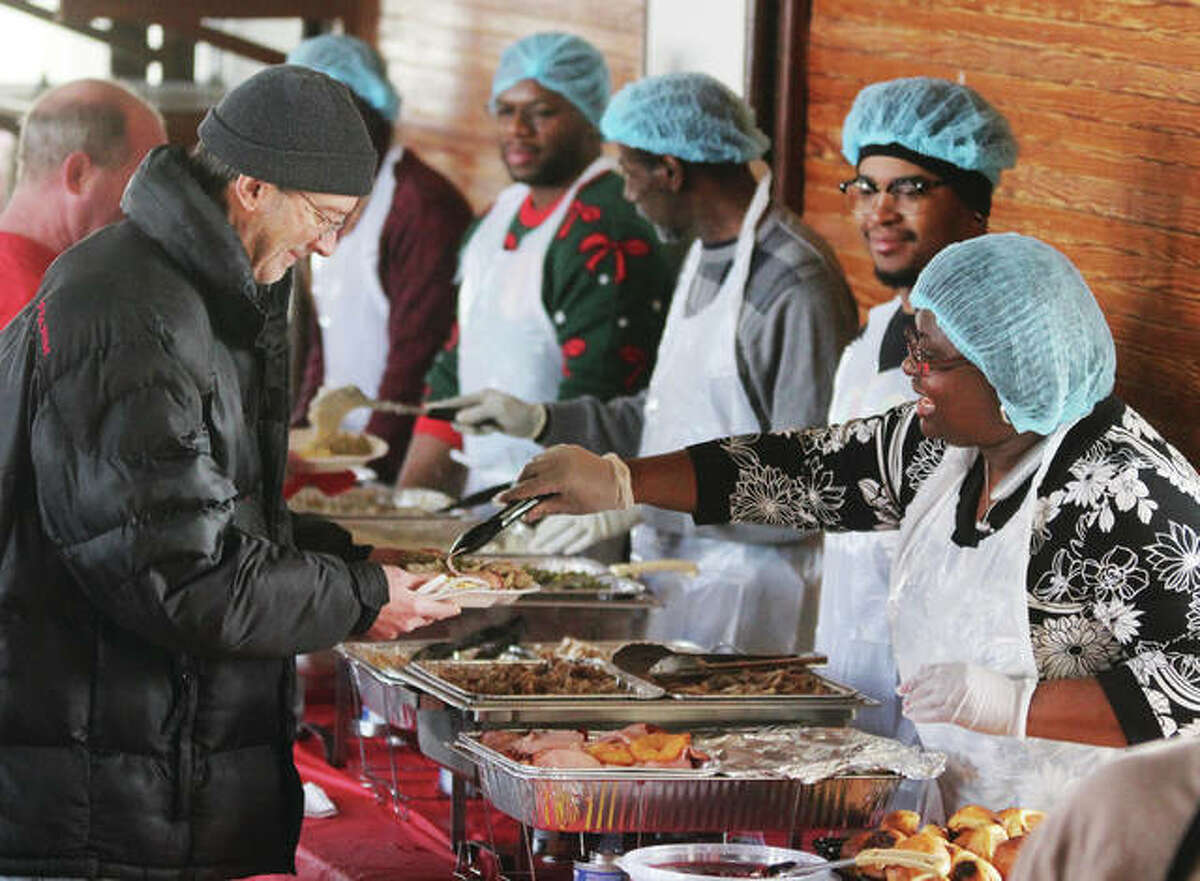 Members of St. John Missionary Baptist Church in Alton serve Christmas dinner. The church, located in the 400 block of Market Street, has been holding the dinner for about five years. Between 75-100 people normally come out to eat.