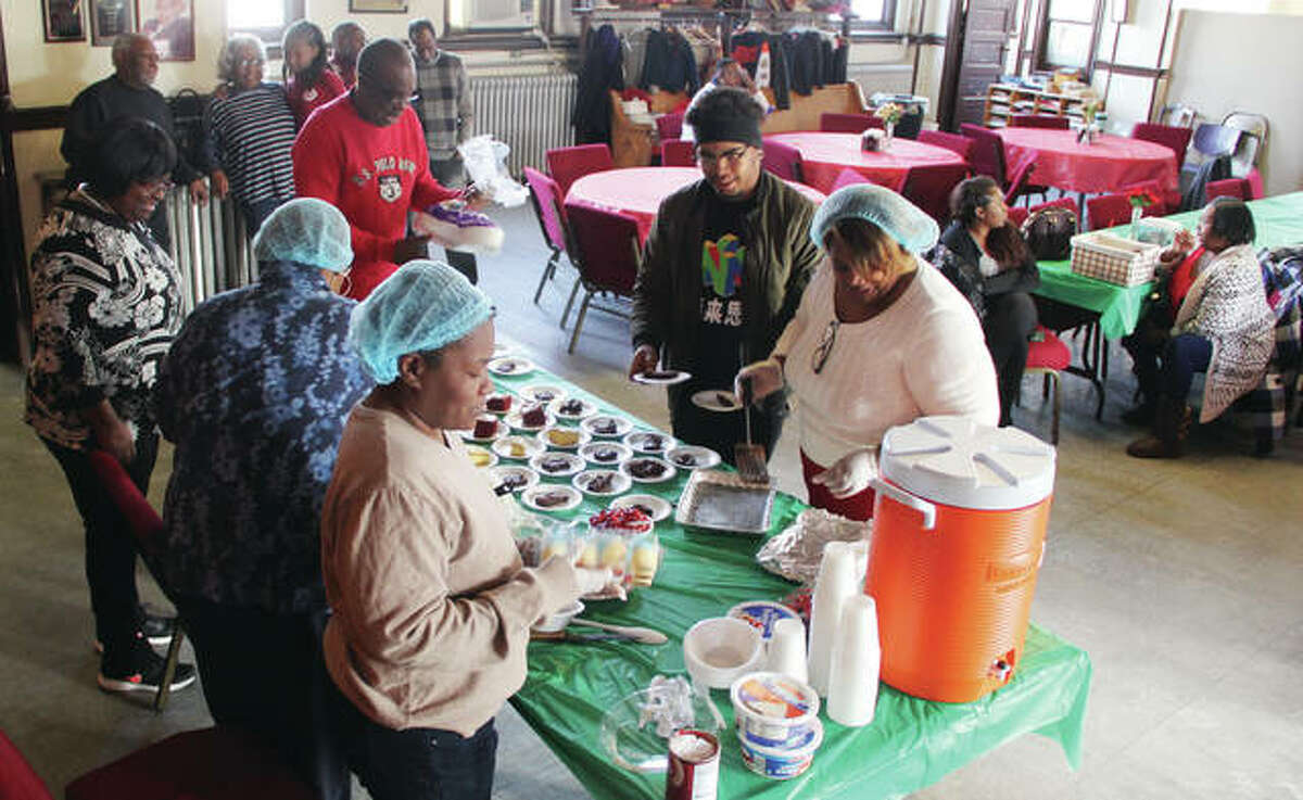 Members of St. John Missionary Baptist Church in Alton cut up desserts for the church's annual Christmas dinner. The church, located in the 400 block of Market Street, has been holding the dinner for about five years. Between 75-100 people normally come out to eat.