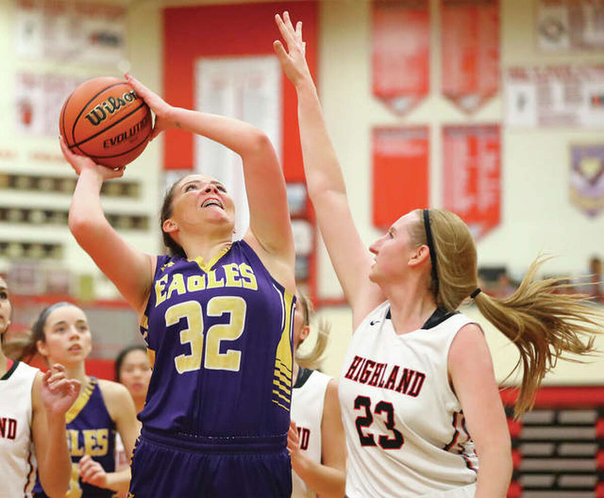 CM's Alaira Tyus (32) goes up for a layup as Highland's Lauren Baer contests the shot in MVC play Dec. 20 in Highland.