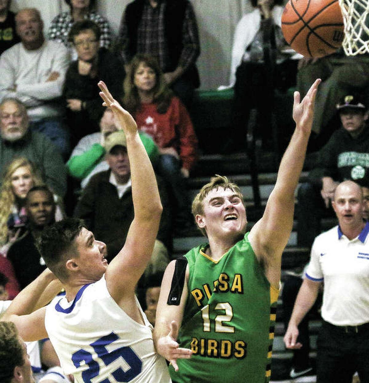 Southwestern's Caleb Robinson (right) slips past Marquette Catholic's Jake Hall to put up a shot during a semifinal game at the Metro East Lutheran Tournament on Nov. 24 in Edwardsville. That loss to the Explorers is the Piasa Birds' lone defeat in a 9-1 start.