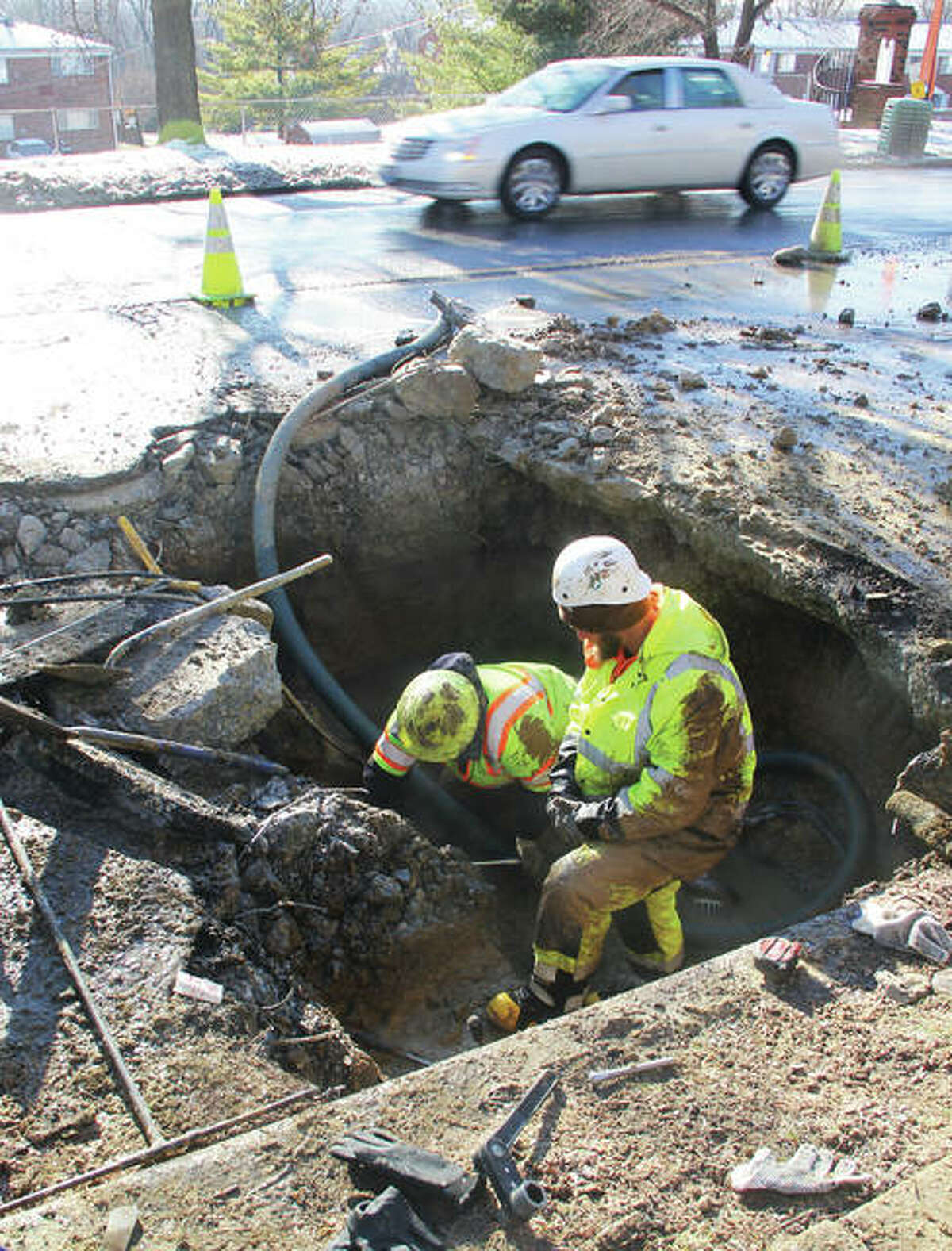 A car goes by as Illinois American Water workers Matt Knight, left, and Brett Becherer work on a water main break on Washington Avenue. Two large breaks were reported Tuesday night and Wednesday morning.