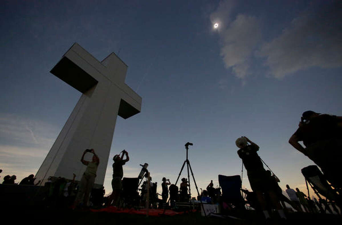 In this Aug. 21, 2017 file photo, a total solar eclipse is seen above the Bald Knob Cross of Peace in Alto Pass, Ill. More than 700 people visited the over 100 foot cross for the event. The first total solar eclipse to sweep coast-to-coast across the U.S. in 99 years drew hundreds of thousands of people to areas of southern Illinois located in the path of totality, where the sun is 100 percent blocked by the sun. The story was chosen as one of Associated Press year's 10 biggest stories or 2017 in Illinois.