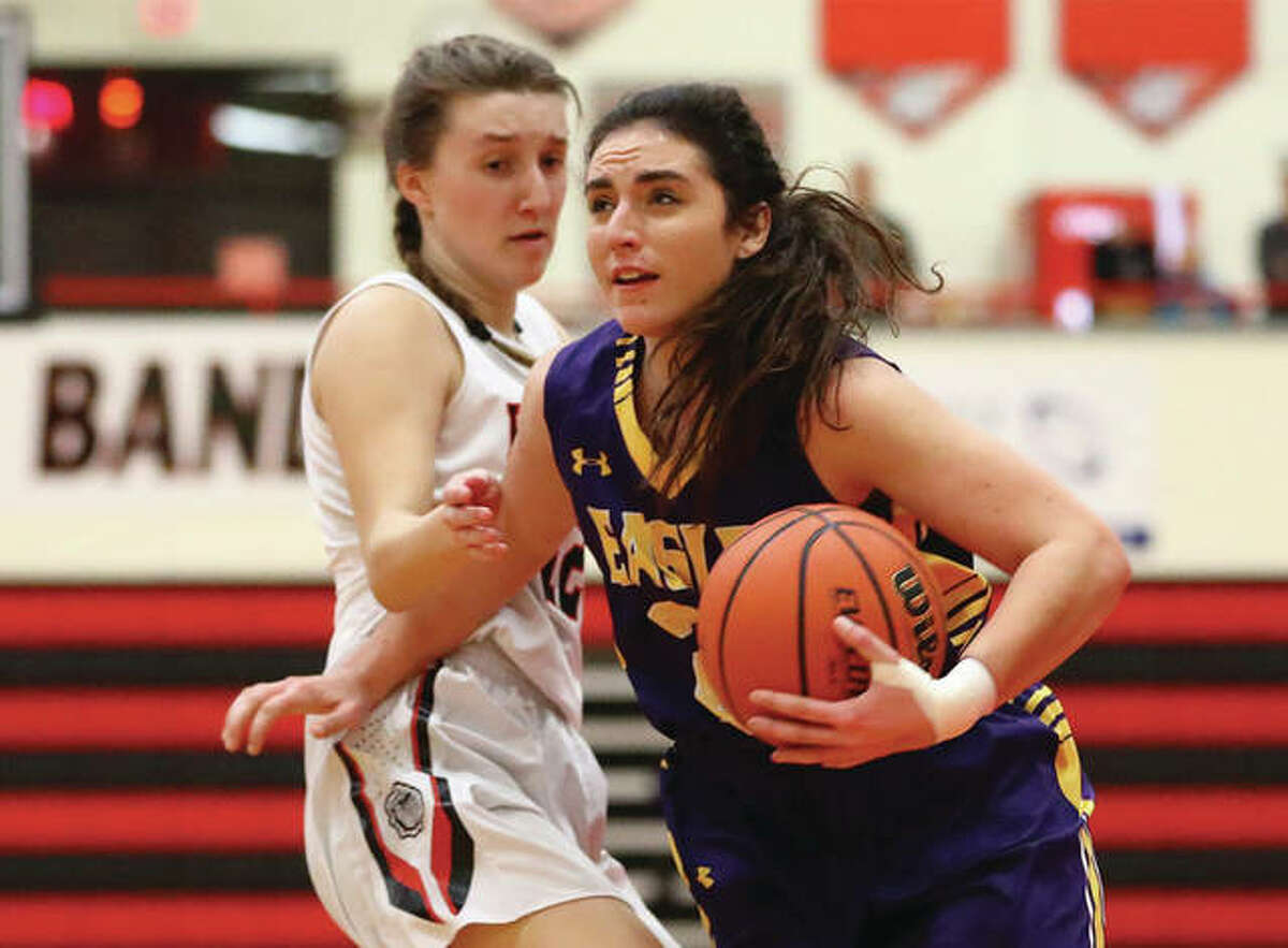 CM's Kaylee Eaton (right), shown driving past Highland's Mae Riffel in a Dec. 20 game at Highland, and her Eagles teammates were back on the road Wednesday to open tourney play in Jerseyville.
