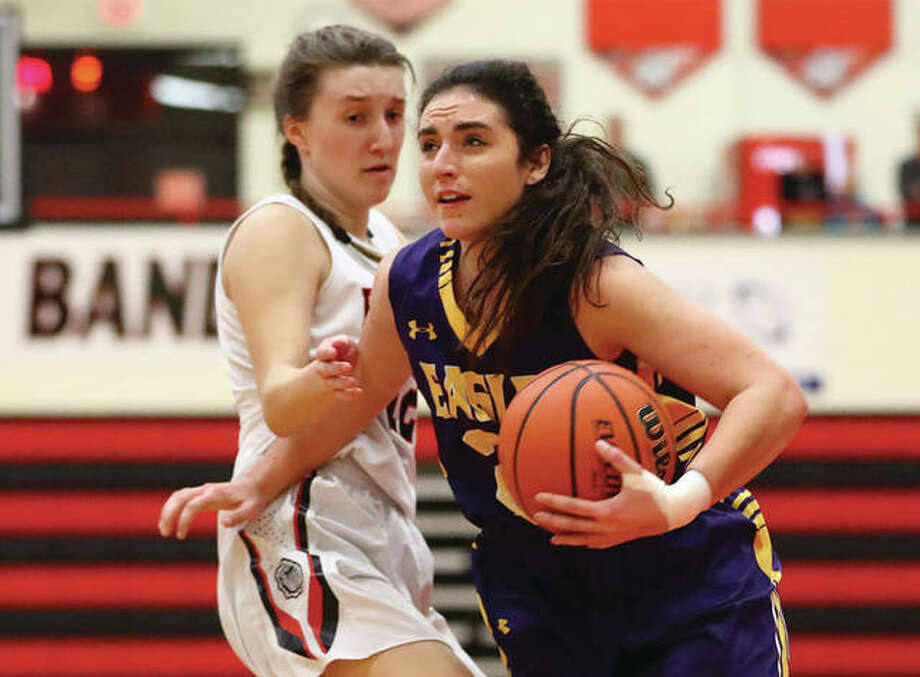 CM's Kaylee Eaton (right), shown driving past Highland's Mae Riffel in a Dec. 20 game at Highland, and her Eagles teammates were back on the road Wednesday to open tourney play in Jerseyville. Photo: Billy Hurst / For The Telegraph