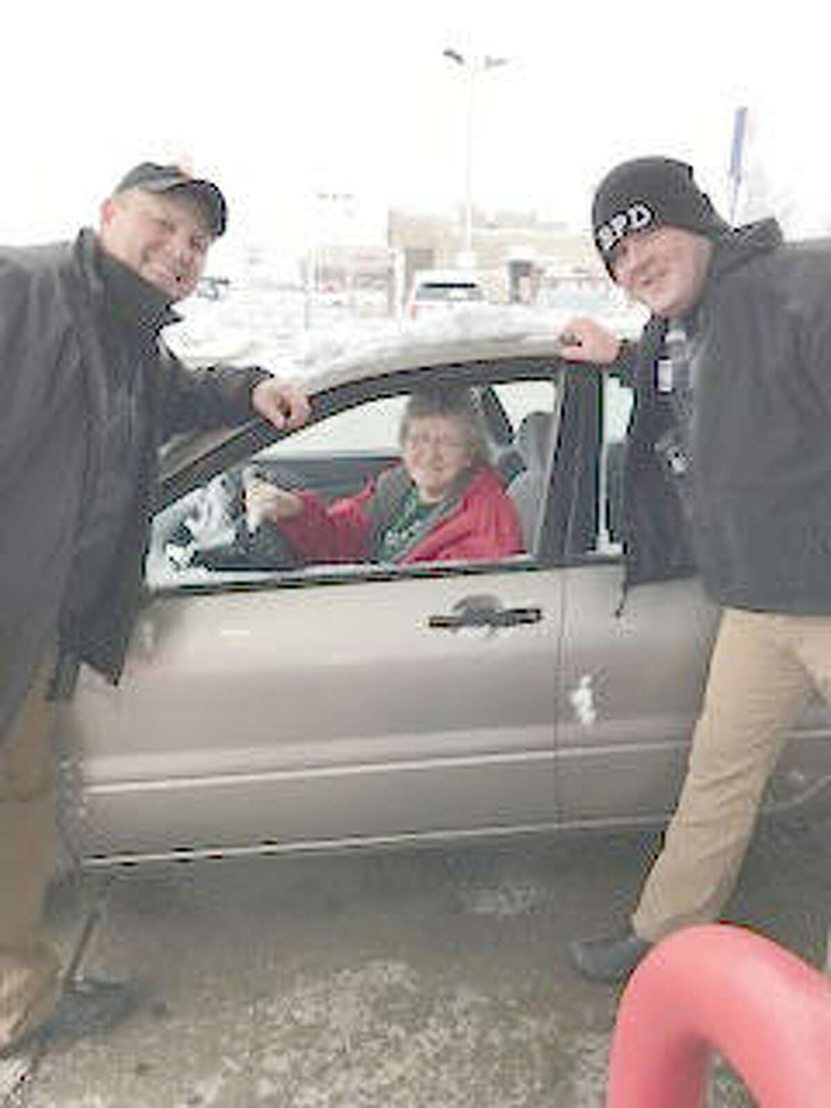 Bethalto Police Chief Greg Smock, left, and another BPD officer pose with a happy recipient of $20 in free gasoline Dec. 23 at the Hit-N-Run in Bethalto, compliments of Mustache March 4PD.