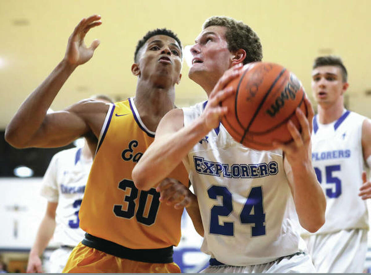 Marquette Catholic's Nick Hemann (24) looks to the basket while Civic Memorial's Jaquan Adams (30) defends during the Explorers' 58-38 victory Nov. 28 in Alton. Both the Eagles and Explorers were in Columbia on Wednesday for opening day of holiday tourney play.