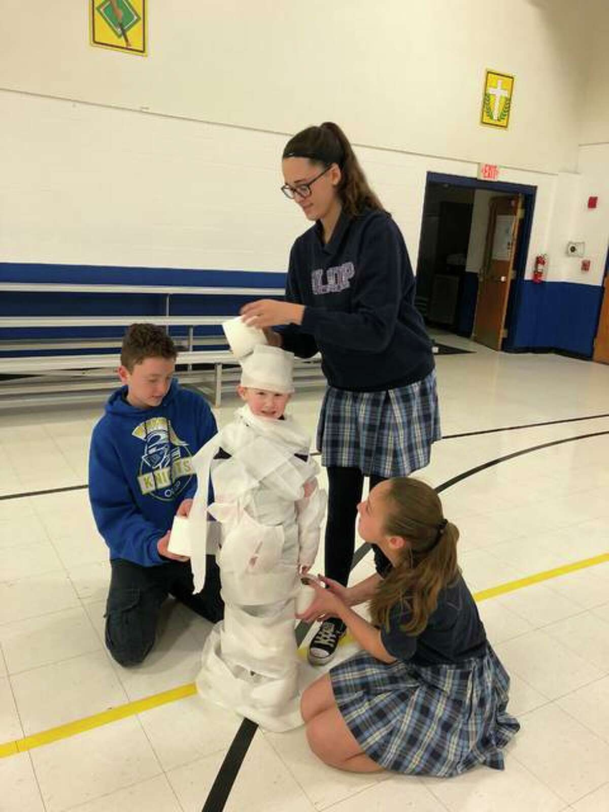 Students, using toilet paper, wrap-up a kindergartner during a recent Christmas party, to make him look like a snowman. The children, students at Our Lady Queen of Peace School, are members of the Buddy Program, which pairs an eighth-grader to help a kindergartner for the year.