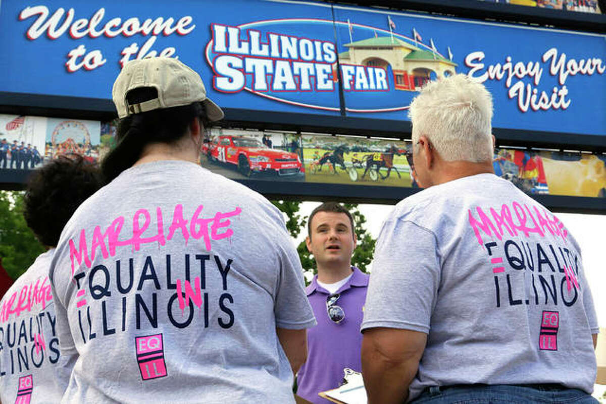 """In this Wednesday, Aug. 14, 2013 file photo, Randy Hannig of Equality Illinois, hands out shirts supporting gay marriage at the Illinois State Fair in Springfield, Ill. Starting in January,2018, Illinois is outlawing a rare criminal defense argument allowing the use of a victim's sexual orientation as justification for violent crime. It's a ban that gay rights advocates hope to replicate in about half a dozen states next year. Illinois follows California in outlawing the so-called """"gay panic defense."""" It isn't common, but one study shows it's surfaced in roughly half of U.S. states since the 1960s."""