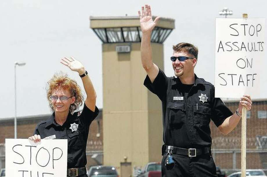 Jacksonville Correctional Officers wave at supporters while walking the picket line in front of the Jacksonville Correctional Center in June 2006. Gov. Bruce Rauner wants to replace guards in state prison watchtowers with security cameras. The Republican's budget office estimates the cost savings at $4 million in the budget year that begins July 1. Corrections spokeswoman Nicole Wilson confirmed that the cameras would replace correctional officers who staff perimeter towers at minimum and medium-security facilities, but didn't have further details. Photo: Seth Perlman | AP