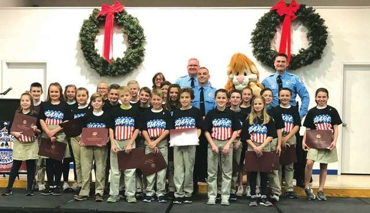 St. Boniface Catholic School fifth-grade students gather with members of the Edwardsville Police Department at the school's D.A.R.E. graduation recently, where students were honored and read their winning essays.