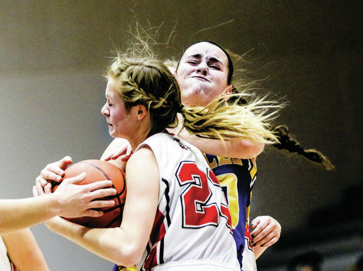 Calhoun's Junie Zirkelbach (front) secures the ball after battling CM's Anna Hall for possession during the final game of pool play in the Jersey Tournament on Thursday night at Havens Gym in Jerseyville.