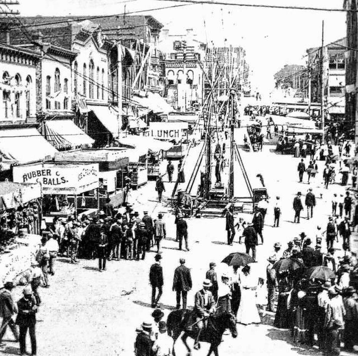 """A festive crowd gathered in Market Square (now Lincoln-Douglas Square) in 1900 for a carnival or exposition. Bunting drapes the Laura Building and other stores along Broadway. Any special event brought out crowds dressed in their finest. Circuses were also popular entertainment for Altonians. Several companies performed through the years at a field on Illinois and Indiana Avenues, now known as """"Dogtown."""""""