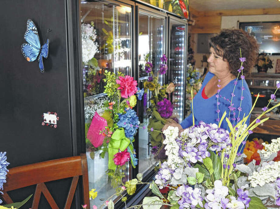 Penny Nagel Fricke looks at some of the flowers in her new floral and garden shop, Penny's Garden Party in Waverly.