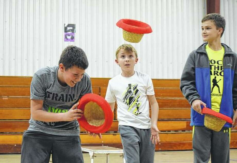 Sixth-graders Landon Fricke (left), Michael Rollins and Warren Legg attempt to flip a hat onto their heads during an assembly where the Fabulous Chinese Acrobats performed on Tuesday. Photo: Samantha McDaniel-Ogletree   Journal-Courier
