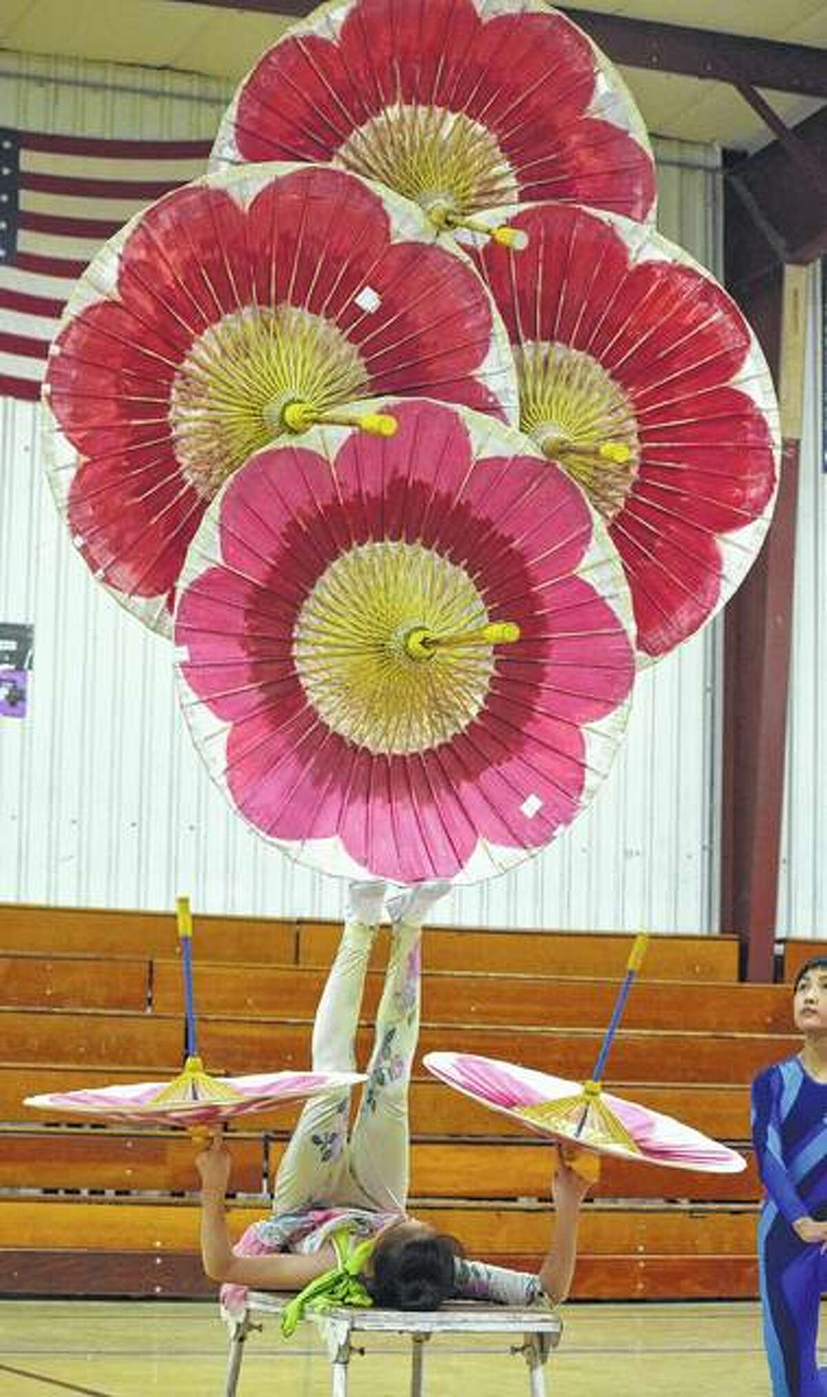 Wang Ling Yue (Ava), 12, a performer with the Fabulous Chinese Acrobats, does a balancing act using Chinese umbrellas Tuesday at North Greene Elementary School.