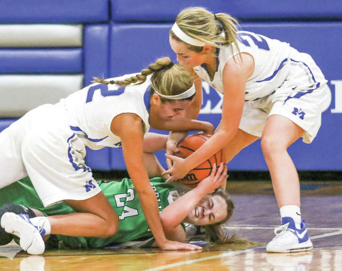 Carrollton's Hannah Krumwiede (bottom) battles Marquette Catholic's Taylor Aguirre and Payton Connors (right) for a loose ball Tuesday night at Marquette High School in Alton.