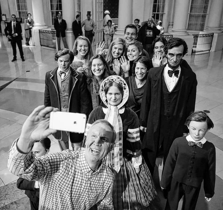 In Jan. 11, 2015 file photo, then Illinois Governor-elect Bruce Rauner takes a selfie with his family and statues of the Lincoln family, at the Abraham Lincoln Museum and Library in Springfield. Gov. Rauner has signed an executive order making the Lincoln Presidential Library and Museum a separate state agency. The Friday order means that the Springfield museum will no longer fall under the Illinois Historic Preservation Agency. AP Photo | Charles Rex Arbogast, File